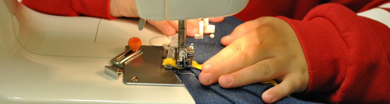 close-up of child's hands using a sewing machine