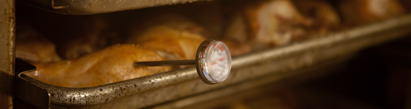 A food thermometer checking the cooking temperature of chicken.